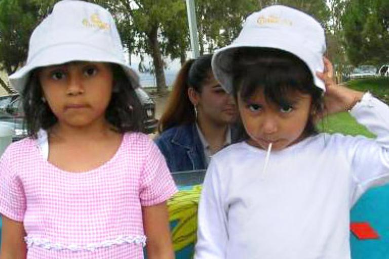 Two Girls Wearing CHAMACOS Hats Looking Curious