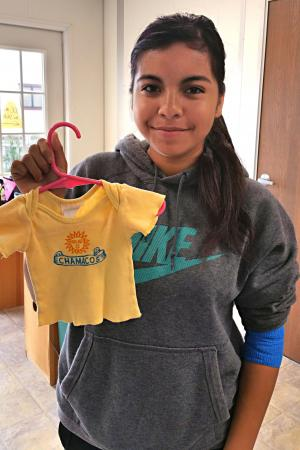 Participant Holds Shirt She was Given as an Infant in Maternity Ward